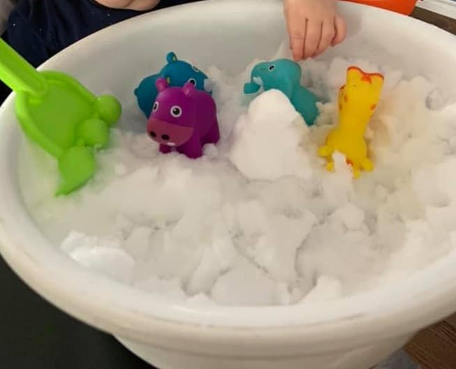 snow sensory bin in a tub with toys