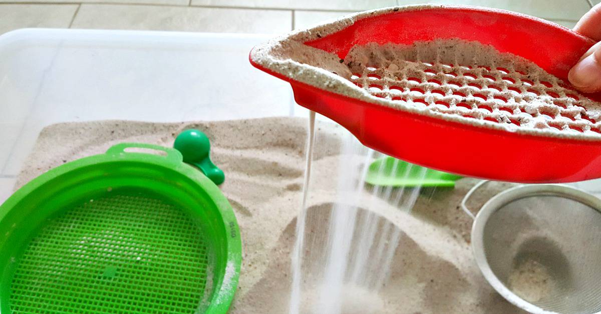 sifting sand through plastic strainer