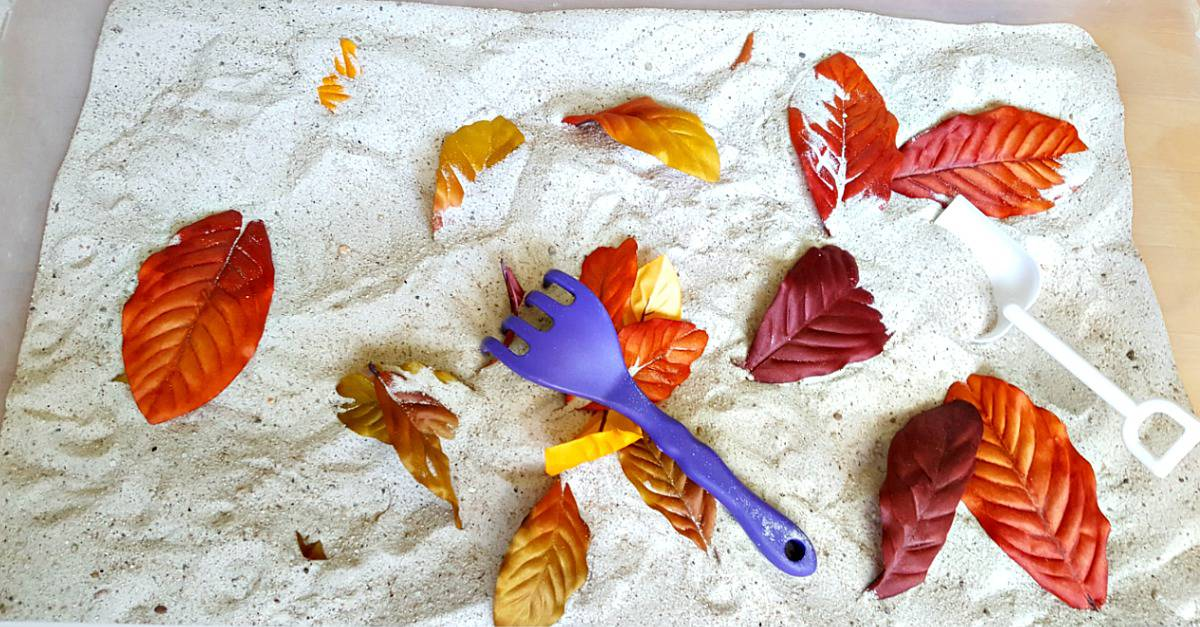 Raking leaves toddler activity in the sandbox