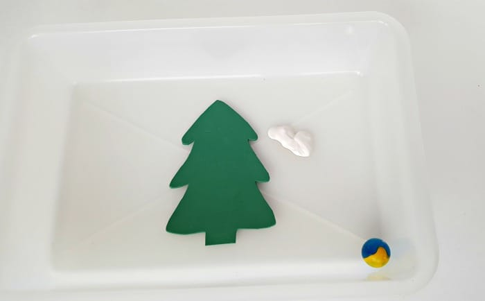 Place tree cutout in plastic bin with white paint and a marble for toddler painting activity