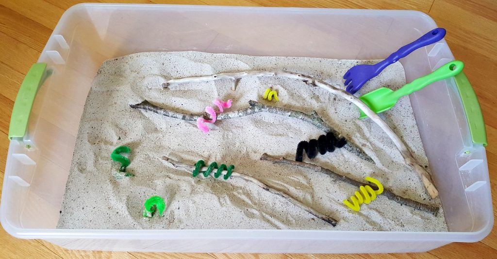 Sensory bin with chenille stem caterpillars and small branches
