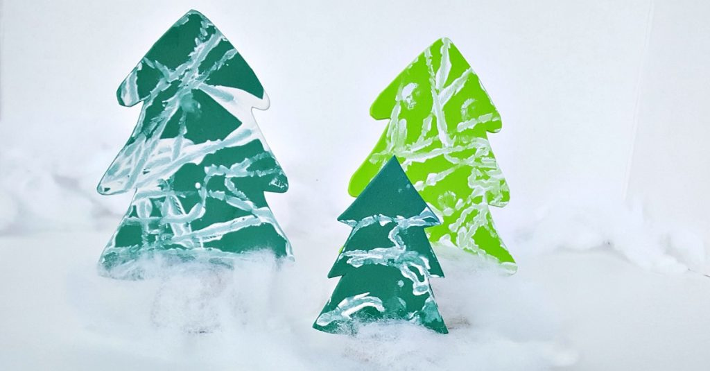Toddler winter activity painting tree cutouts with a marble in white paint