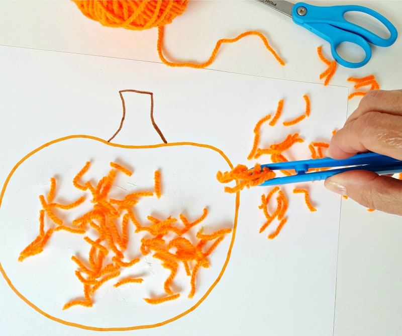 Sprinkle yarn pieces over pumpkin cut out with tongs