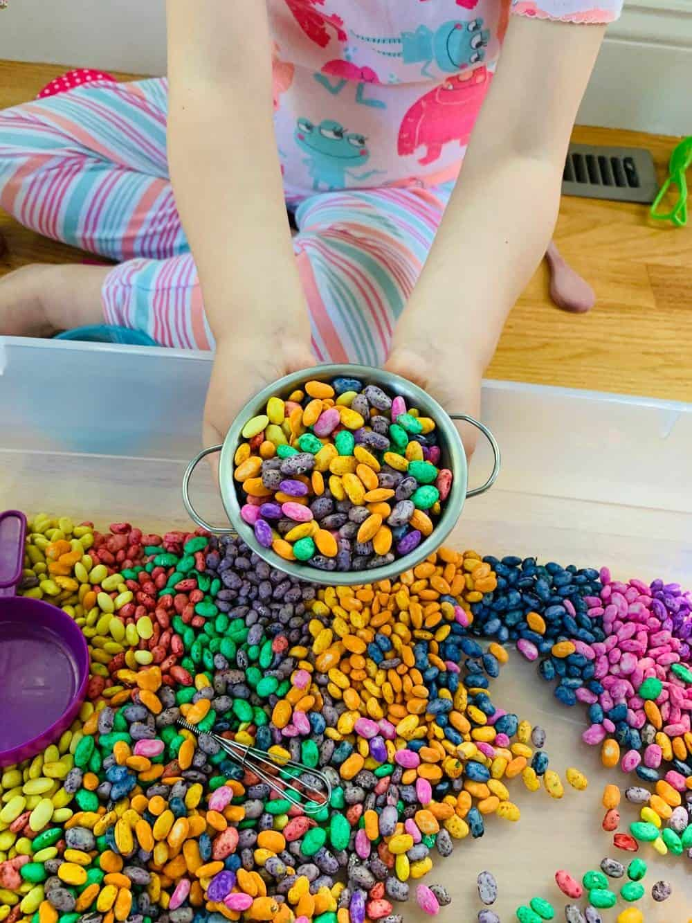 playing with magic beans dyed and colored for a sensory bin